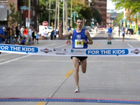 Dominic Maio finishes first in the men's division at the finish line to Briggs & Al's Run & Walk for Children's Hospital of Wisconsin near the Summeriest grounds on Saturday. In 38 years the event has raised more than $18 million. In 2015 there were 15,400 participants.