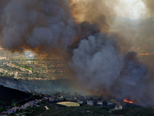 A wildfire approaches homes on Wednesday, May 14, 2014, in San Marcos, Calif. Flames engulfed suburban homes and shot up along canyon ridges in one of the worst of several blazes that broke out Wednesday in Southern California during a second day of a sweltering heat wave, taxing fire crews who fear the scattered fires mark only the beginning of a long wildfire season. (AP Photo)