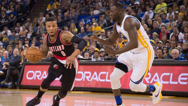 April 3, 2016; Oakland, CA, USA; Portland Trail Blazers guard Damian Lillard (0) dribbles the basketball against Golden State Warriors forward Draymond Green (23) during the first quarter at Oracle Arena. Mandatory Credit: Kyle Terada-USA TODAY Sports