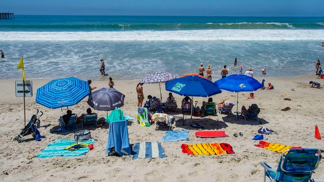 With most of Southern California's coastline shut down for the Fourth of July holiday due to a spike in coronavirus cases, the beach in San Clemente, Calif., remains open as crowds, socially distanced, fill the sand Saturday, July 4, 2020.