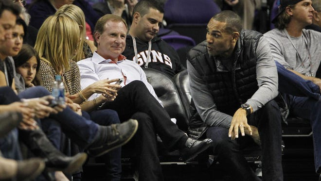 Grant Hill, right, visits with Phoenix Suns  Owner Robert Sarver in the 2nd half of an NBA game on Nov. 27, 2013.