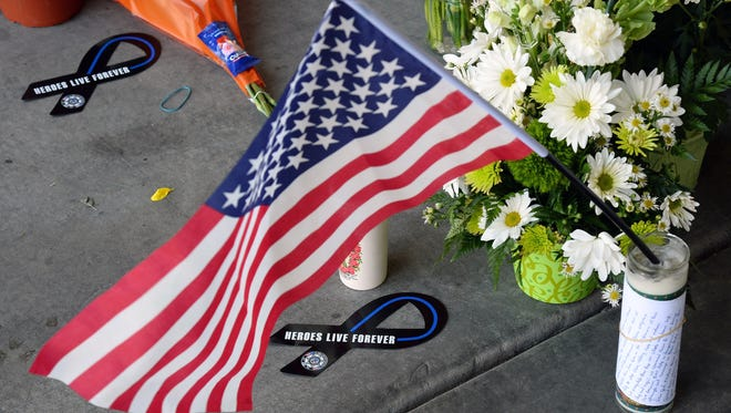 Items sit at a memorial outside CiCi's Pizza on June 9, 2014 in Las Vegas, Nevada. The Las Vegas Metropolitan Police Department said officers Alyn Beck and Igor Soldo were shot and killed at the restaurant by Jerad Miller and his wife Amanda Miller yesterday. Police said the Millers then went into a nearby Wal-Mart where Amanda Miller killed Joseph Wilcox before the Millers killed themselves.