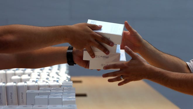 Apple Store employees pass boxes of the  Apple iPhone 5S in September  2013 in Palo Alto, Calif.