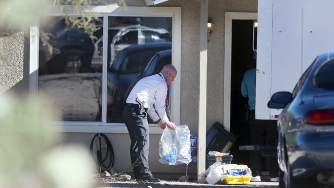 Tucson Police Department investigators and evidence technicians investigate the scene at a home where two people were arrested Nov. 26, 2013, after three girls told authorities that they have been imprisoned for possibly the past two years, in Tucson, Ariz.