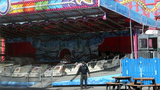 A workers uses a blower at Playland amusement park in Rye Thursday as the park readied to open Saturday.