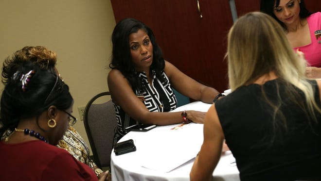 "Former ""The Apprentice"" star Omarosa Manigault talks with fellow Trump supporters at the Quality Inn & Suites in Bellville for the Trump-Pence Women's Empowerment Tour in Ohio on Saturday."