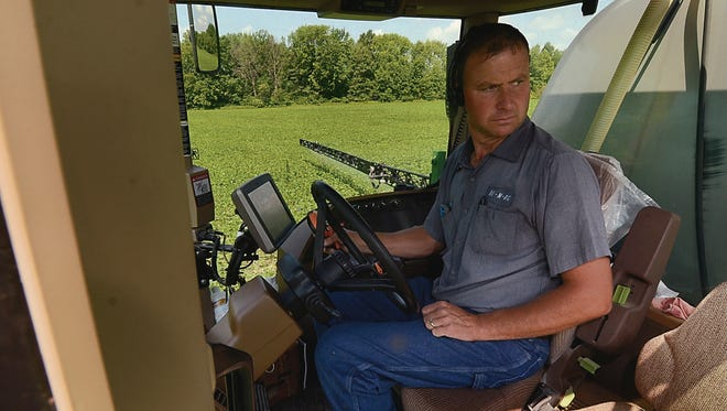 In this July 7, 2017 photo, Brad Burbrink keeps an eye on the swath of his sprayer visually and with the aid of a spraying program as he tends to one of BE N AG's fields near Blackhawk, Ind. Nearly every day, two semi-loads of food-grade corn leave the BE N AG Family Farm from southern Vigo County en route to an Azteca milling site in Evansville.