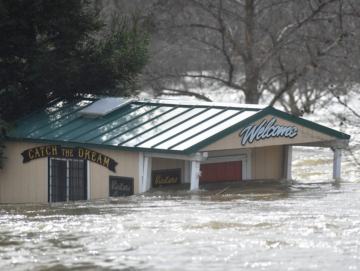 A building is partially submerged in flowing water