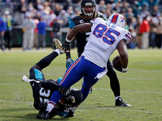 Jacksonville Jaguars free safety Tashaun Gipson, lower left, tackles Buffalo Bills tight end Charles Clay (85) after a reception in the first half of an NFL wild-card playoff football game, Sunday, Jan. 7, 2018, in Jacksonville, Fla. (AP Photo/Stephen B. Morton)
