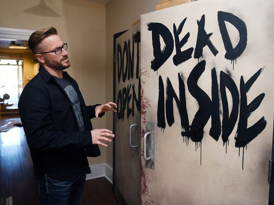 """James Frazier shows doors that were used in one of the scenes of AMC show, """"The Walking Dead.""""  Frazier is opening a comic store and offices on Main Street in downtown Franklin.  The 36-year-old Thompson's Station resident is the founder of Fanfest.com, which puts on events for fans of the popular AMC show, """"The Walking Dead."""""""