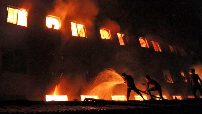 Bangladeshis and firefighters battle a fire at a garment factory in the Savar neighborhood in Dhaka, Bangladesh, Nov. 24, 2012.
