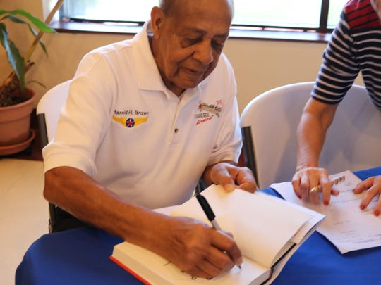 Former Tuskegee Airmen retired Lt. Colonel Dr. Harold Brown signs a copy of his new book.