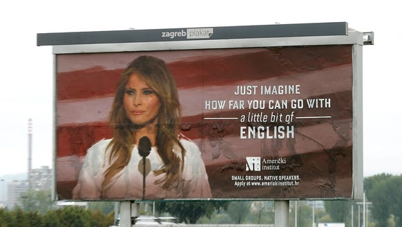 Cars drive behind a huge billboard for the 'American