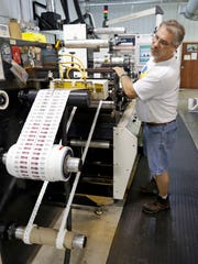 InkWorks Printing's John Hoppe inspects a run of sequential labels for a customer Thursday September 3, 2015 in Plymouth.