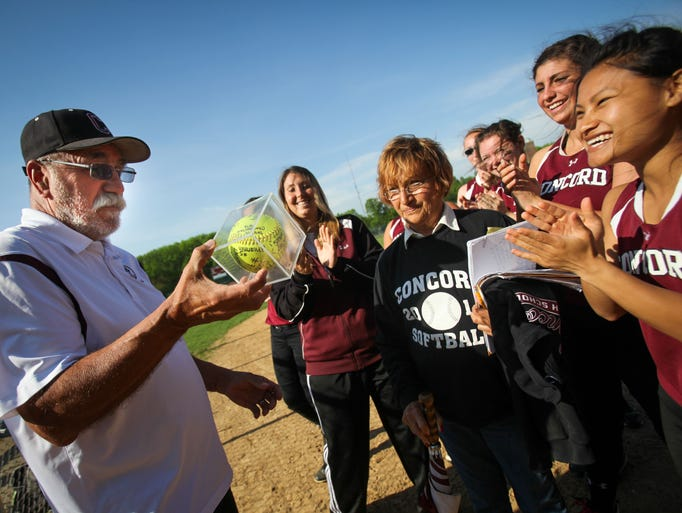 Concord softball coach George Kosanovich receives a game ball signed by his players after coaching his last home game as Concord plays host to Newark Tuesday, May 13, 2014. Kosanovich coached the softball team for more than twenty years, and also coached the football and wrestling teams.