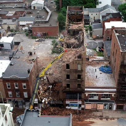 Demolition crews work to take down a collapsed building