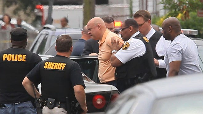 Neptune police Sgt. Philip Seidle is taken into custody after he shot his ex-wife to death on Ridge Avenue in Asbury Park.