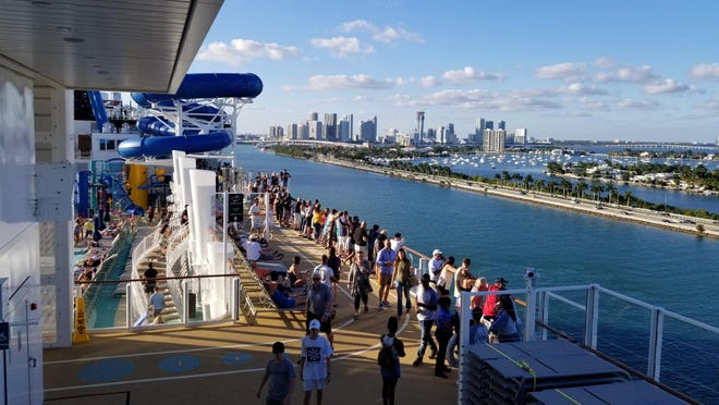 Passengers watch as the Encore departs from the PortMiami.