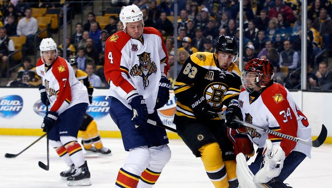Boston Bruins left wing Brad Marchand (63) fights for position against Florida Panthers defenseman Dylan Olsen (4) and goalie Tim Thomas (34) as the puck squirts away during the second period.