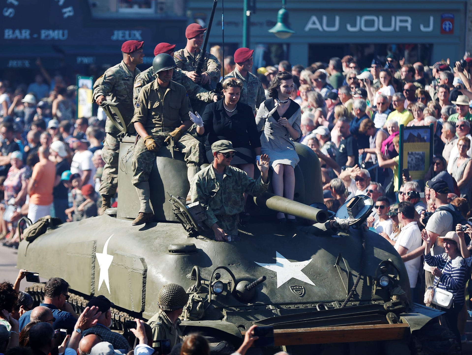 World War II enthusiasts sit on a tank during a parade