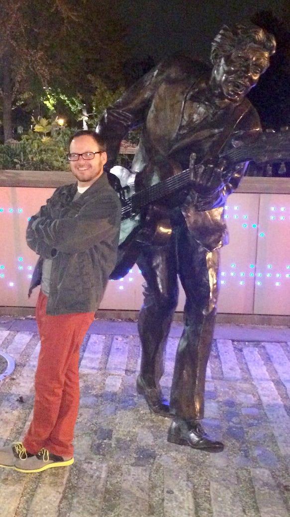 Music columnist Brian Passey stands near the statue