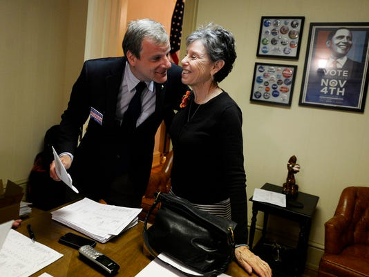 """Incumbent city council member Michael Helfrich hugs his treasurer Rebecca Cook as he called his race as one of the top three during the primary election Tuesday, May 19, 2015. Kate Penn â """" Daily Record/Sunday News"""