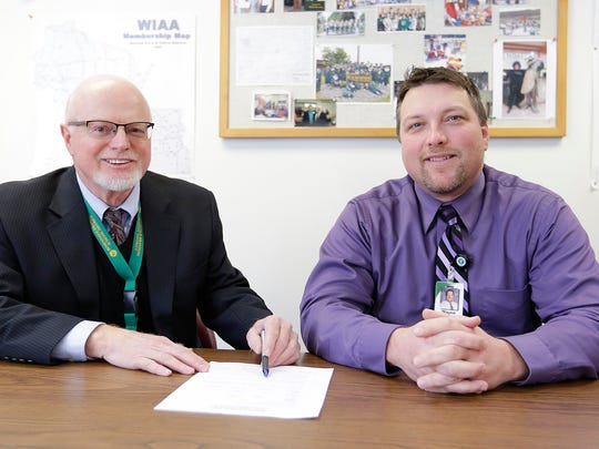 Gary Hansen and Wayne Weber go over a contract that instates Weber as the new superintendent for the Rosendale-Brandon School District beginning June 30. Weber is currently principal of the Laconia/Cirrus School.