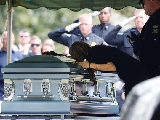 The wife of Greenville City Police Officer Allen Jacobs leans over his casket at the graveside service at Coleman Memorial Cemetery in Travelers Rest on Thursday, March 24, 2016.