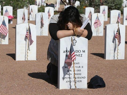 Cristina Sturtz kneels before the grave of her grandmother,