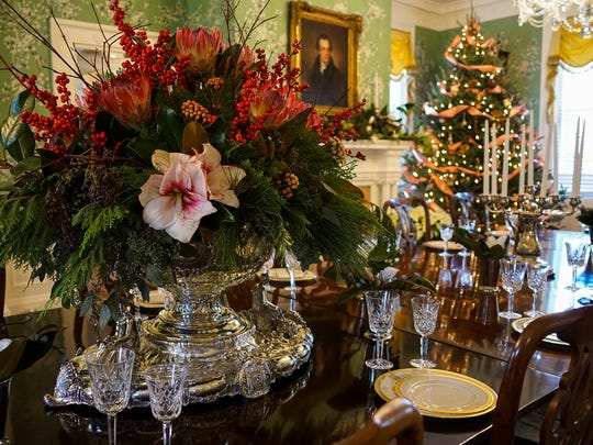 Beautiful floral arrangements of holiday amaryllis, winterberries and greenery adorn the dining room table.