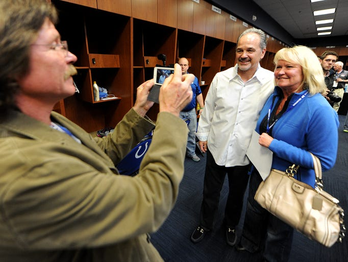 Sheri Alexander has her photo taken by her husband Mike Alexander with Indianapolis Colts coach Chuck Pagano inside the locker room during the Chuckstrong Tailgate Gala at the Indiana Farm Bureau Football Center, Friday, May 2, 2014, in Indianapolis.