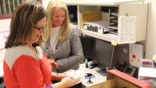 Probate Court staff Heather Smothers, foreground, and Circuit Court Administration clerk Kristi Cox, pack supplies - including snacks, batteries, personal hygiene products and more - in two of five boxes the departments mailed Wednesday to active U.S. Army personnel serving in the Middle East.