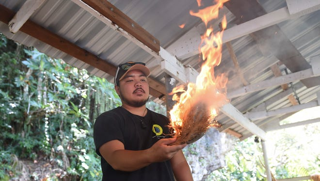 Fire maker Keith Manglona observes his creation at the Valley of the Latte Adventure Park in Talofofo on March 11, 2018.