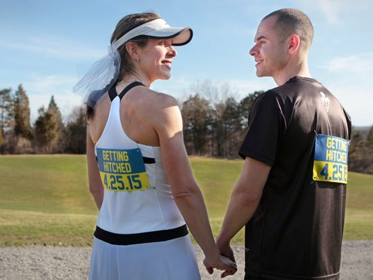 Heather Danielson and Chris Patterson pose in their wedding-themed running gear at Cobbs Hill Reservoir Wednesday in Rochester. The pair, who met while training for the Boston Marathon, will run Boston next Monday, then get married the following Saturday, April 25th.