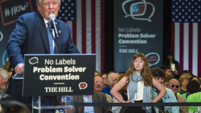 Lauren Batchelder of Chester N.H. waits for Donald Trump to stop talking after interrupting her and to continue with her question on women's rights at the No Labels Problem Solver Convention in Manchester N.H. on Monday, October 12, 2015.