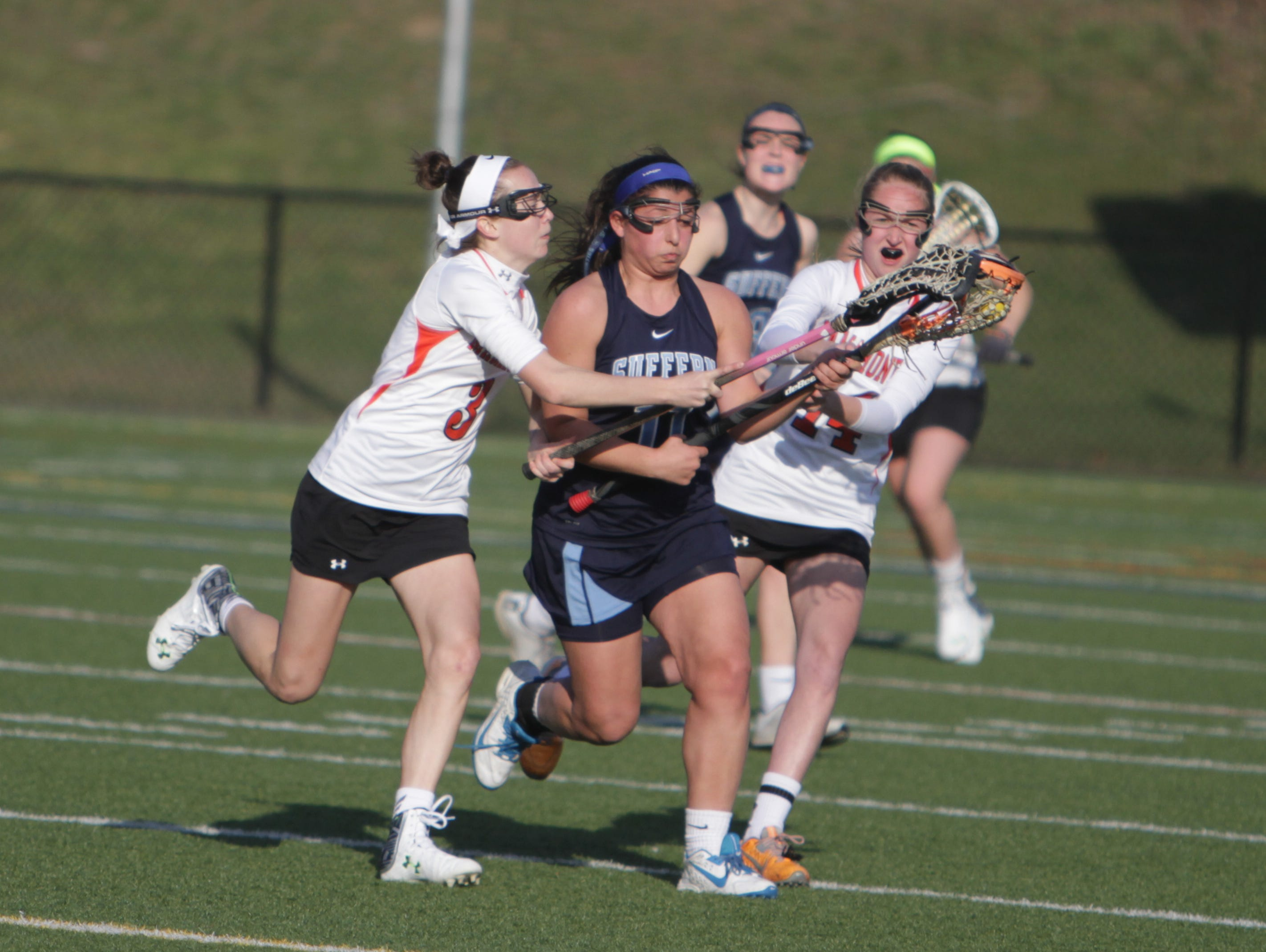 Suffern's Alli Iodice is defended on by Mamaroneck's Madeline Riodan (3) and Sophie Artz (14) during a Section 1 girls lacrosse game between Suffern and Mamaroneck at Mamaroneck High School on Tuesday, March 22nd, 2016. Suffern won 16-3.
