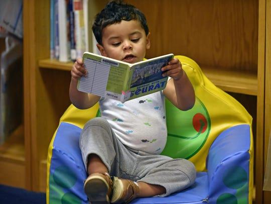 Joniel Delgado, 2, of Vineland opens a few books while