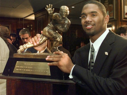 Michigan's Charles Woodson poses with the Heisman Trophy after becoming the first primarily defensive player ever to take the honor Dec. 13, 1997, at the Downtown Athletic Club  in New York.