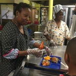 J.S. Clark Elementary School food service technician Jacqueline Smith serves lunch Monday.