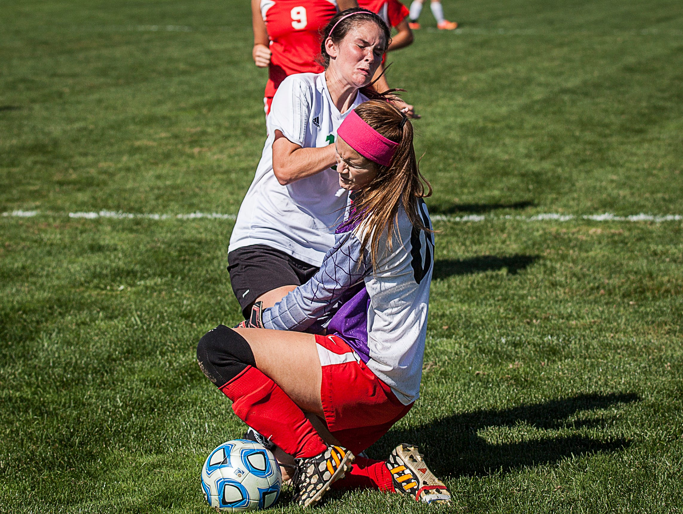 Yorktown's Lizzie Smith collides with Jay County goalie Lilly Rogers during their game at the Yorktown Sports Park on Saturday, Oct. 10, 2015.