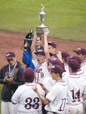 Mount Abraham's Chris Wood (9) raises the trophy after his team's 11-1 win against Bellows Falls in the Division II baseball state championship game on Saturday at Centennial Field. AUSTIN DANFORTH/FREE PRESS