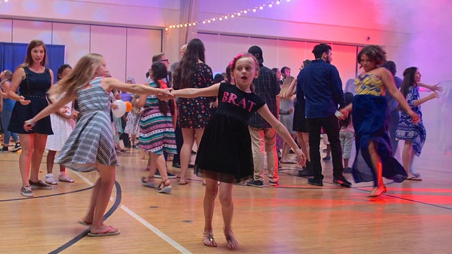 Campers dance during an indoor campfire event in Palm Desert, Friday. The Palm Desert YMCA holds the dance after evacuating campers from the Big Bear campsite on Wednesday.