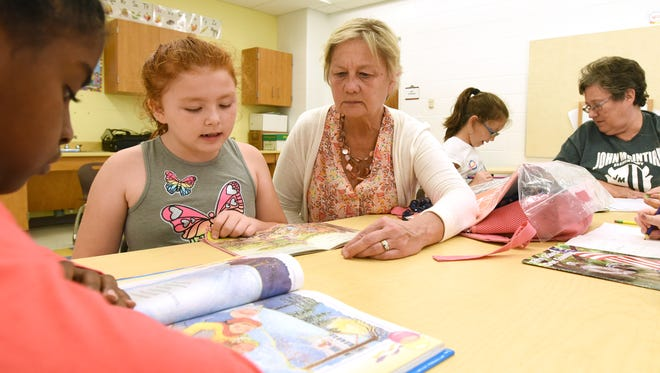 Mary Fenton reads with Olivia Quintero, left, while Catherine Haynes reads with Ashtynn Ehrnfield at John McIntire Elementary School's after school program. At left is Ariyah Sullens.