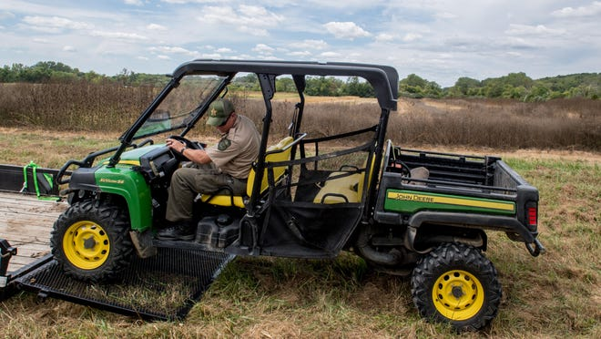 Conservation Police Sgt. Scott Avery of the Illinois Department of Natural Resources unloads a UTV for use Sunday in a recovery operation on Banner Marsh property near Glasford. Human remains were found Saturday along the Illinois River bank in the area, and officers from Peoria County, IDNR and the Peoria Police Department were searching the area.
