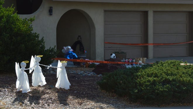 Angel figurines made by neighbors stand outside an Albuquerque home Wednesday, Dec. 7, 2016, where police say a gunman fatally shot three children and shot their mother before turning the gun on himself. Authorities said George Daniel Wechsler, 45, shot and killed the three children Monday evening as their mother frantically tried to protect them.