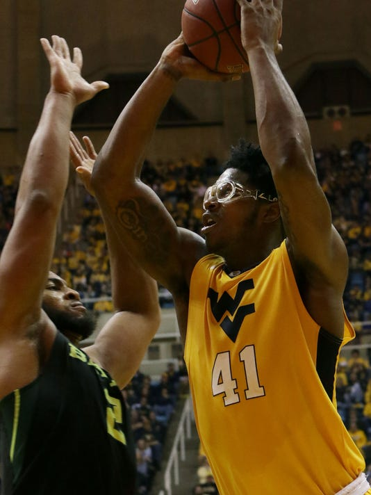 West Virginia forward Devin Williams (41) drives to the basket while guarded by Baylor forward Rico Gathers (2) during the second half of an NCAA college basketball game, Saturday, Feb, 6, 2016, in Morgantown, W.Va. (AP Photo/Raymond Thompson)