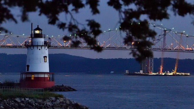 The 1883 Lighthouse at Sleepy Hollow at on the Hudson River at sundown, backed by the Tappan Zee Bridge.