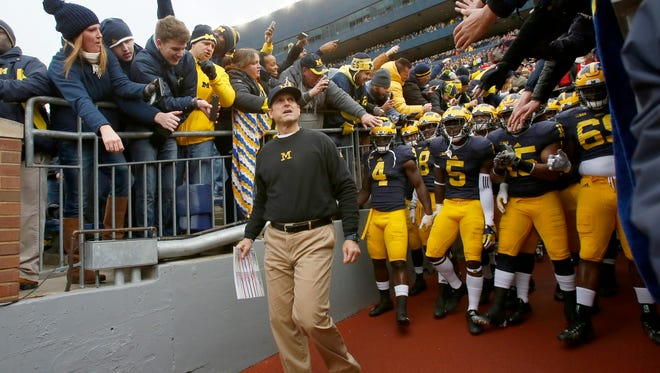Michigan head coach Jim Harbaugh leads his players out the tunnel for their football game against Ohio State on Saturday, November 28, 2015, in Ann Arbor.
