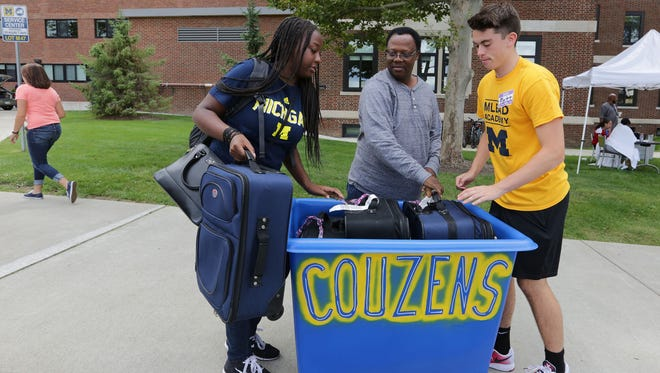 Giselle Uwera,  of Grand Rapids is an incoming freshman at the University of Michigan, loading her luggage from the car to a roller carrier being held by freshman Matt Haldeman of Newton, Pa. , as  her  dad, Gerard Uwihoreye,  helps with another bag in  front of  Couzens Hall on the campus of University of Michigan in Ann Arbor Thursday, Sept. 1, 2016