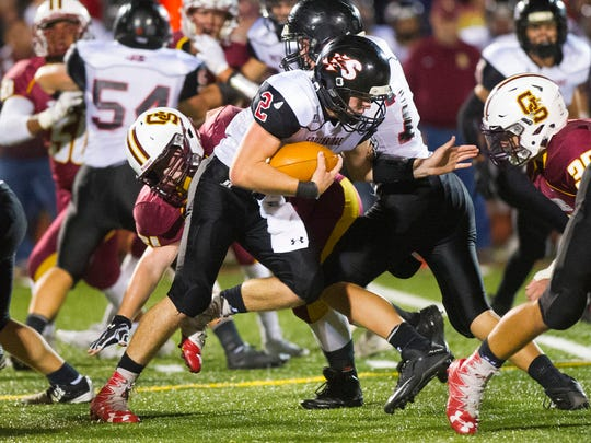 Southridge's Jayce Harter (2) runs the ball between Gibson Southern defenders during their game at Jewell Memorial Field in Fort Branch, Friday, Oct. 14, 2016. Gibson Southern beat Southridge 38-35.